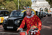 Anti Brexit protester dressed up as a clown version of Prime Minister Boris Johnson hires a Boris bike in Westminster and cycles along The Mall as it is announced that Boris Johnson has had his request to suspend Parliament approved by the Queen on 28th August 2019 in London, England, United Kingdom. The announcement of a suspension of Parliament for approximately five weeks ahead of Brexit has enraged Remain supporters who suggest this is a sinister plan to stop the debate concerning a potential No Deal.