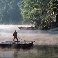 A boatman pulls a raft through morning mist to an island hotel on Phewa Tal Lake, near Pokhara, Nepal.