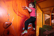 Indoor children's playground child climbs a wall