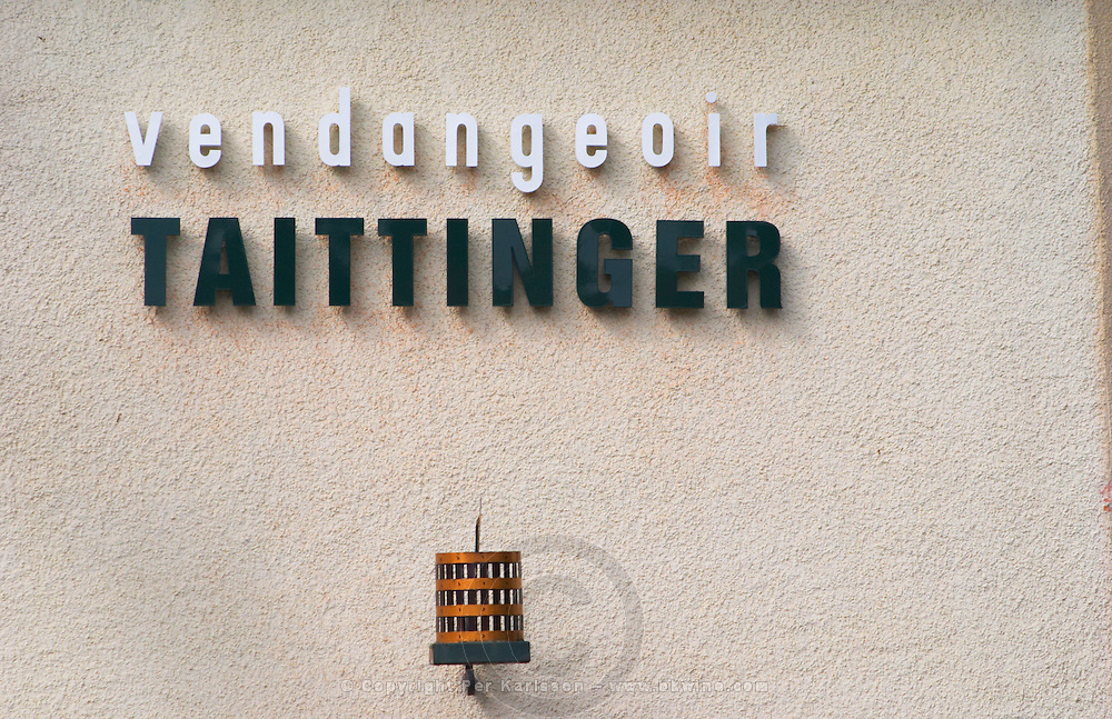A wrought iron painted sign that illustrates the theme of champagne and wine production: a traditional vertical basket wine press on the vendangeoir Taittinger (wine press house in the vineyard), the village of Hautvillers in Vallee de la Marne, Champagne, Marne, Ardennes, France