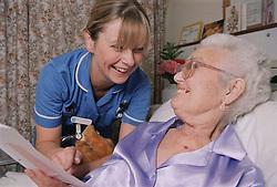 Staff Nurse sharing a joke with elderly patient on medical ward,