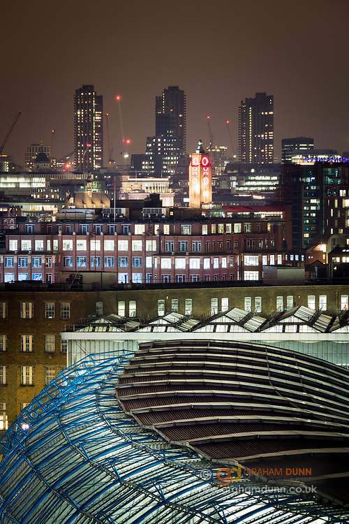 The curved roof of Waterloo Station, with the Oxo Tower and the Barbican tower blocks in the distance. A London urban landscape captured at night from an elevated viewpoint. England, UK.