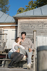 Young couple sitting boathouse jetty drinking beer