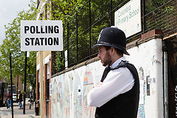 © Licensed to London News Pictures. 07/05/2015. London, UK. A police officer stands outside a polling station station in Columbia Road, Tower Hamlets, east London today. Photo credit : Vickie Flores/LNP