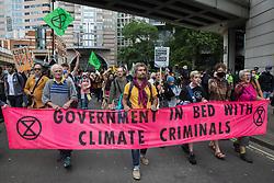 Environmental activists from Extinction Rebellion stage a Blood Money March through the City of London during the fifth day of Impossible Rebellion protests on 27th August 2021 in London, United Kingdom. Extinction Rebellion were intending to highlight financial institutions funding fossil fuel projects, especially in the Global South, as well as law firms and institutions which facilitate them, whilst calling on the UK government to cease all new fossil fuel investment with immediate effect.
