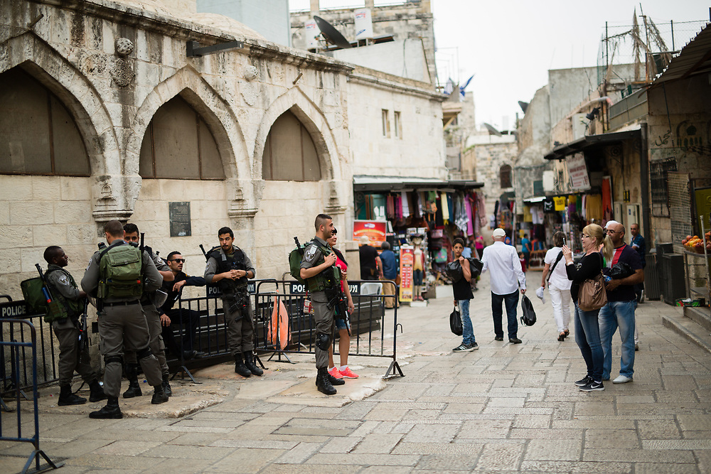 An Israeli Border Police Man poses for a photograph with tourists as other border policemen stand guard at HaGai Street, or al Wad Street in the Muslim quarter of the Old City of Jerusalem, Israel, on April 10, 2016.