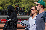 A muslim woman in a niqab is used to masking - Battersea Park is reasonably busy,  and generally people maintain some social distance, as the sun is out and it is warmer. The 'lockdown' continues for the Coronavirus (Covid 19) outbreak in London.