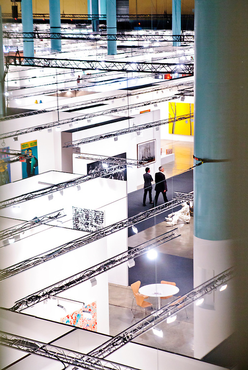 Aerial view of a two men walking in the sprawling main exhibition hall at Art Basel Miami Beach 2010