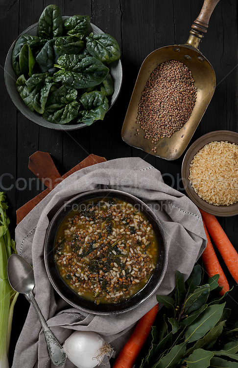Minestrone with fresh spinach rice and brown lentils on black wooden background top view shot