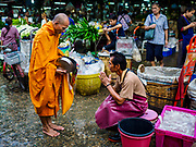 "04 DECEMBER 2018 - BANGKOK, THAILAND:  A fish seller gives alms to a Buddhist monk in front of a pile of plastic bags in Khlong Toei market. The issue of plastic waste became a public one in early June when a whale in Thai waters died after ingesting 18 pounds of plastic. In a recent report, Ocean Conservancy claimed that Thailand, China, Indonesia, the Philippines, and Vietnam were responsible for as much as 60 percent of the plastic waste in the world's oceans. Khlong Toey (also called Khlong Toei) Market is one of the largest ""wet markets"" in Thailand. December 4 was supposed to be a plastic free day in Bangkok but many market venders continued to use plastic.    PHOTO BY JACK KURTZ"