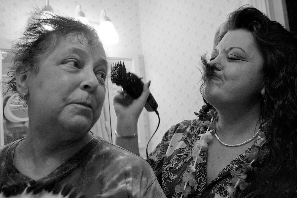 MIDDLEBURY, CT - 24 DECEMBER 2007 -112008JT12-.Tracie Marcil makes a fake mustache from her mother Marie's recently shorn locks at Marie's house in Middlebury on Christmas Eve 2007. Having gone through her fourth round of chemotherapy, this was Marie's second time having her head shaved since being diagnosed with stage four lung cancer. The hair cut followed a tropical-themed Christmas party at the empty house that was put up for sale after Marie was diagnosed..Josalee Thrift / Republican-American