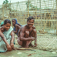 Homeless village woman from Bangladesh make bamboo lath for a duck pond at Mirpur Destitute Camp near Dhaka, 1977.  They had been had left destitute and violated  by  back-to -back cyclone and a  brutal 1971 war of independence