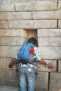 The Listening wall, A tourist chanting in the listening wall, Machu Picchu, Cusco Region, Urubamba Province, Machupicchu District in Peru, South America