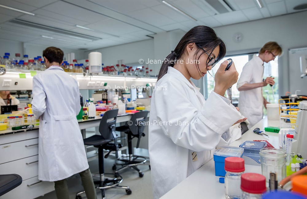 Nederland, Amsterdam, 26 juli 2017.<br /> Het Microbiologisch Lab van VUmc.<br /> De microbiologen van de UvA verhuisden vorig jaar voor een half miljoen euro naar de VU en nu moeten ze weer terug. Waarheen is nog niet duidelijk want hun oude lab is alweer bezet. Dat is balen, en vooral voor de aio's (assistent in opleiding) want die hebben allemaal een tijdelijk contract en zien hun onderzoekstijd nu opgaan aan heen en weer verhuizen. Edward en Alejandro moeten met hun gevoelige microscopen opnieuw aan de wandel.<br /> <br /> Foto: Jean-Pierre Jans