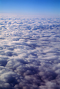 Looking down on clouds from above with blue sky.