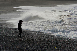 © Licensed to London News Pictures. 15/11/2020. Aberystwyth, UK. People walk on the beach as strong winds and massive waves batter the Welsh seaside resort of Aberystwyth in Ceredigion, UK. Photo credit: Graham M. Lawrence/LNP