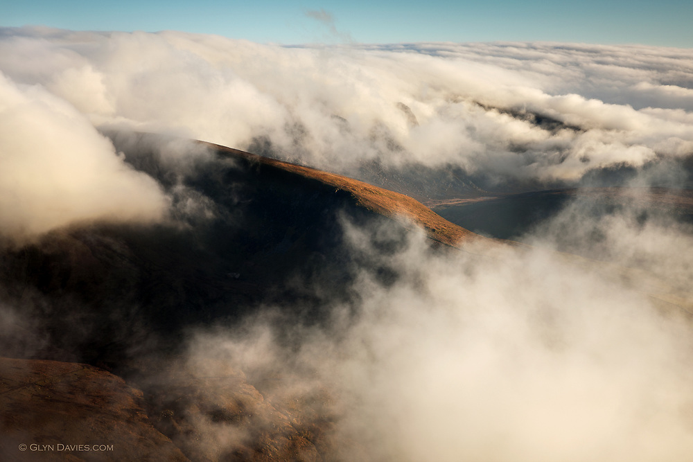 Banks of cloud roll in from the Irish Sea and curl over the top of the Nantlle Ridge in Snowdonia, North Wales before evaporating again over the valley. Taken from the adjacent mountain, Mynydd Mawr.