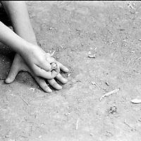 Boy playing with marbles..Because of the war, fathers have disappeared or have been killed often being replaced as head of the family by their young son...During the summer1999, over 245,000 Serbs and Roms fled to Serbia and Montenegro from or within Kosovo in fear of reprisals from the majority Albanian population, after NATO air strikes had forced the withdrawal of Yugoslav. In 2003, less than 2% of them had returned and a large number of these internally displaced persons (IDPs) were still living in camps in very difficult conditions..In addition, around 5,000 IDPs, mainly of Roma ethnicity, are living in unrecognized collective centres, makeshift huts, corrugated metal containers and other substandard shelters. .This work was meant to look at how the life of children and young adults is affected by the fact that they are IDPs. I asked myself more specifically what would be different for these children/young adults from the 'normal' people of their age as far as education, health, social life, family, 'love' life and leisure are concerned. ..Garçon jouant aux billes..A cause de la guerre, des pères ont disparus ou ont été tués et sont remplacés par leur jeune fils à la tête de la famille...Pendant l'été 1999, plus de 245 000 serbes et roms ont fuit le Kosovo pour chercher refuge en Serbie ou au Montenegro, par peur de représailles de la part de la majorité de la population albanaise après que les forces de l'OTAN aient forcé l'armée yougoslave à se retirer. En 2003, moins de 2% d'entre eux étaient rentrés chez eux et le plus grand nombre de ces 'déplacés' (IDPs) vivaient encore dans des centres d'accueil dans des conditions très difficiles..Environ 5 000 IDPs, la plupart romas, vivent dans des centres non reconnus faits de containers ou d'abris de fortune. .Ce travail s'est focalisé sur les jeunes IDPs, sur les conséquences de leur état de 'déplacés' sur leur vie et plus particulièrement dans les sphères concernant l'éducation, la santé,  la vie sociale, la vie d