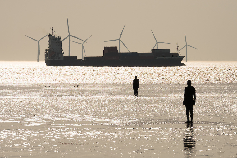 """A container ship passes Crosby Beach into the Irish Sea, after leaving Liverpool on the river Mersey.  Two sculptures by the artist Sir Antony Mark David Gormley, OBE look on, positined as they are for his landscape artwork, """"Another Place"""""""