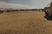 Tchikuteny?s big family gather in a cue, chanting after leaving the church. In Angola?s Namibe desert, at Giraul, in the Namibe province, Tchikuteny, from the Mucubal tribe, is the leader of a big family, maybe the biggest family in the world.<br /> He is the chief leader, the manager and responsible for the entire village. <br /> In his village, Tchikuteny lives nowadays with most of his big family, his 33 wives, that were once 43, but 10 left the village, and most of their descendants.<br /> Tchikuteny maintains the registry of all the new-borns, totalizing 154 sons, and his grandsons, that are around 60. Nowadays, 4 new babies are on the way, and 3 great grand children were born recently.<br /> Huge harmony, love and respect transpire in the village atmosphere. The sense of a community is the pillar of their sustainability and sustenance and their autonomy depends prominently on cattle and agriculture that is made by the villagers. Nevertheless, Tchikuteny village is in close connection with their surrounding communities. Children attend Giraul School and there is proximity and relations with the extended family that lives in the surroundings.<br /> Being the spiritual leader of the community, Tchikuteny is also responsible for the weekly religious works that happens in the village church. <br /> This big family opened his doors to share with us their daily lives.