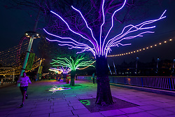 "© Licensed to London News Pictures. 07/12/2020. LONDON, UK. A runner passes ""Lumen"" by David Ogle, trees illuminated with glowing neon flex. Preview of ""Winter Light"" presented by Southbank Centre.  Over 15 artworks and new illuminated commissions by a range of leading international artists are on display around the site's buildings and the Riverside Walk until the end of February 2021.  Photo credit: Stephen Chung/LNP"