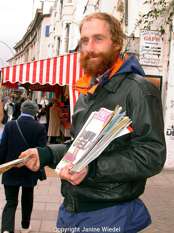 Big Issue seller in local town selling paper in street...