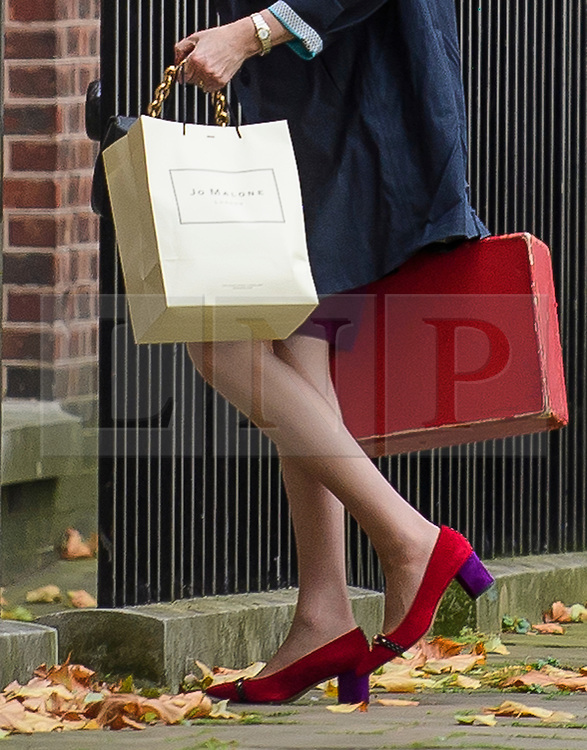 © Licensed to London News Pictures. 16/10/2017. London, UK. Prime Minister Theresa May is seen carrying a Jo Malone shopping bag and her red box while entering Downing Street by the back door. Later Mrs May and Brexit Secretary David Davis will have dinner with EU chief negotiator Michel Barnier and Commission chief Jean-Claude Juncker in Brussels after Brexit talks were described as being in deadlock. Photo credit: Ben Cawthra/LNP