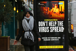 © Licensed to London News Pictures. 20/01/2021. London, UK. A woman without wearing a protective face covering walks past the government's 'Don't Help The Virus Spread' publicity campaign poster in north London, after the mutated variant of the SARS-Cov-2 virus continues to spread around the country. On Tuesday 19 January, 1,610 people died in the UK within 28 days of a positive Covid-19 test. This is the biggest figure reported in a single day in the UK since the pandemic began last year. According to government figures over 4.2 million people have now received the first dose of a vaccine. Photo credit: Dinendra Haria/LNP