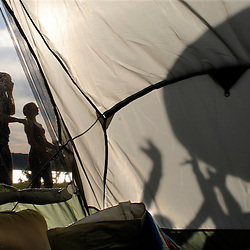 Meladeh Rabie, 16, and her sister, Amber, 12, wait for the Ammar sisters (seen in the shadows against the tent) to toss the ball to them during the play of a volley-ball-like game (played with a giant ball) at the Ammar family farm on the banks of the Potomac River in Bryan's Road, Maryland...Photo by Susana Raab..