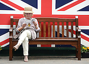 © Licensed to London News Pictures. 01/06/2012. Epsom , UK A woman reads a race programme sitting on a bench. Ladies Day today 1st June 2012 at Epsom 2012 Investic Derby Festival. The Queen will attend tomorrow's race meet as part of the 60th Jubilee celebrations. Photo credit : Stephen Simpson/LNP