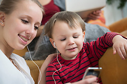 Sister listening to mp3 player with her brother, smiling