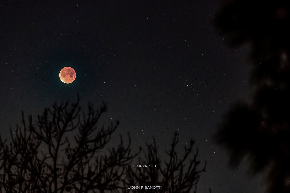 The fully eclipsed moon on the moring if January 31, 2018 appears to the left of the open cluster, M44 in the constellation of Cancer