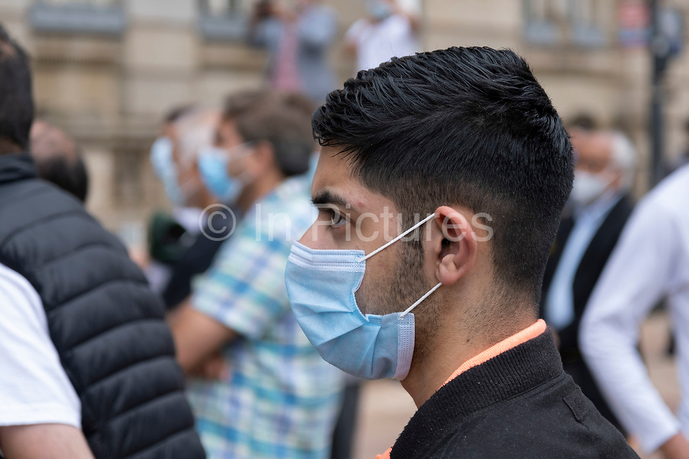 Young man wearing a face mask, which became compulsory in shops on the 24th July, in the city centre on 5th August 2020 in Birmingham, United Kingdom. Coronavirus or Covid-19 is a respiratory illness that has not previously been seen in humans. While much or Europe has been placed into lockdown, the UK government has put in place more stringent rules as part of their long term strategy, and in particular social distancing.