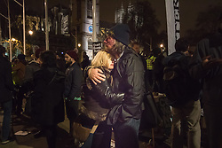 Westminster, London, December 2nd 2015.  As Parliament prepares to vote on air strikes on Islamic State terrorists in Syria, Stop The War and other groups opposed to British military involvement protest outside Parliament. PICTURED: A couple embrace after hearing the result of the vote. ///FOR LICENCING CONTACT: paul@pauldaveycreative.co.uk TEL:+44 (0) 7966 016 296 or +44 (0) 20 8969 6875. ©2015 Paul R Davey. All rights reserved.