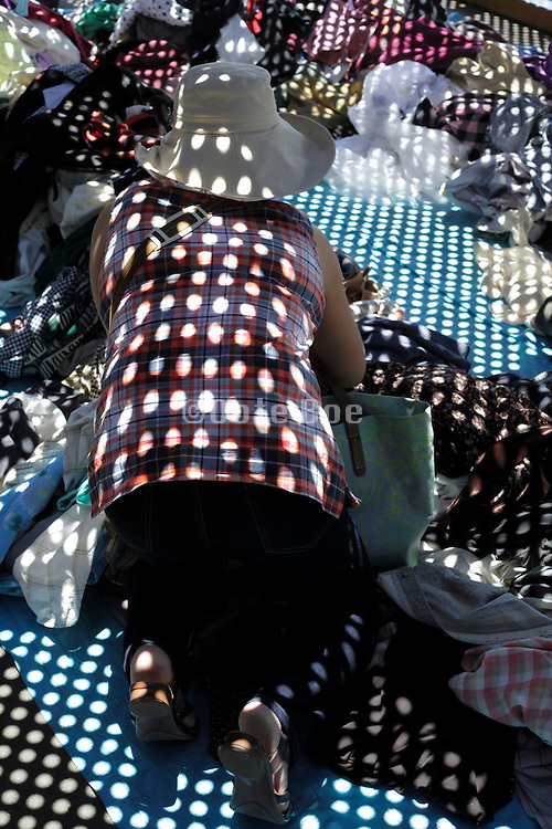 woman looking for clothing at a flea market with grating shadow projection