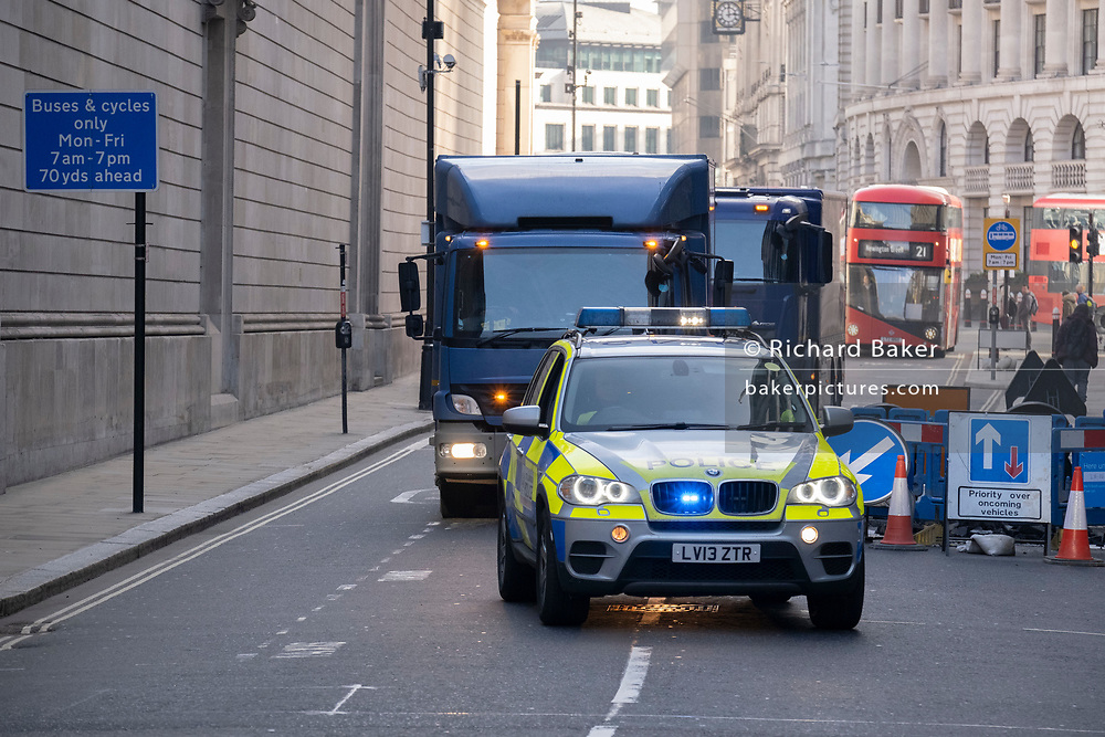 With streets blocked off, a convoy of heavy high-security vehicles carrying high-value assets is accompanied by an armed escort of police officers towards the Bank of England, on 1st March 2021, in London, England.