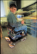 "Driving with a joystick, MIT graduate student Joseph Spano takes a spin in the ball-wheelchair he is helping to design. The chair, which uses spheres instead of wheels, automatically compensates for movement, if Spano reaches down, the chair responds by thrusting out its ""wheels"" to prevent him from toppling over. From the book Robo sapiens: Evolution of a New Species, page 180."