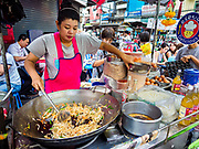 "18 MAY 2017 - BANGKOK, THAILAND:   A vendor makes ""phat Thai"" (also called ""Pad Thai"") at a street food stall in Bangkok's Chinatown. Phat Thai is fried rice noodles and Thailand's unofficial national dish. City officials in Bangkok have taken steps to rein in street food vendors. The steps were originally reported as a ""ban"" on street food, but after an uproar in local and international news outlets, city officials said street food vendors wouldn't be banned but would be regulated, undergo health inspections and be restricted to certain hours on major streets. On Yaowarat Road, in the heart of Bangkok's touristy Chinatown, the city has closed some traffic lanes to facilitate the vendors. But in other parts of the city, the vendors have been moved off of major streets and sidewalks.    PHOTO BY JACK KURTZ"
