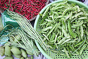 Fresh fruit and vegetables including snake beans and red chillies for sale at Daeum Kor morning market in Phnom Penh, the capital city of Cambodia. A large variety of local products are available for sale in fresh markets all over Cambodia, all being sold on small individual stalls.