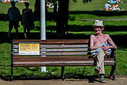 Old people enjoy a break on the benches - People enjoy the sun on Clapham Common after the Government eased restrictions and allowed people to meet - Lambeth Council have replaced signs to say stay alert and to allow people sit on benches. The 'lockdown' continues for the Coronavirus (Covid 19) outbreak in London.