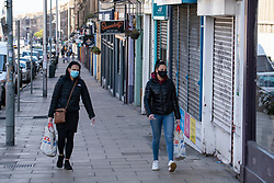 Edinburgh, Scotland, UK. 1 May 2020. Views of Edinburgh as coronavirus lockdown continues in Scotland. Streets remain deserted and shops and restaurants closed and many boarded up. Pictured; two women wearing face masks walk along Leith Walk with most shops and restaurants closed and shuttered. Iain Masterton/Alamy Live News