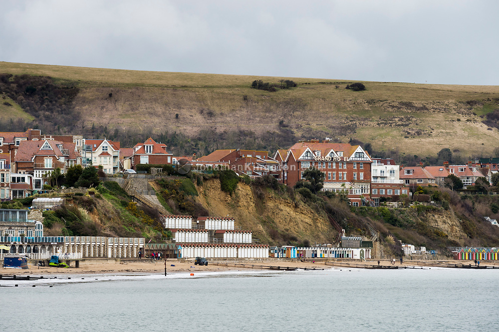 Beach huts line the shore in the coastal town Swanage, England.