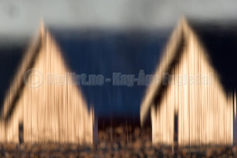 Two boathouses photograped through water, then mirrored   To naust som er fotografert via vann, og derettter speglet.