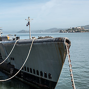 In the foreground is the USS Pampanito (SS-383), open to public visitors and moored on San Francisco's Fisherman's Wharf. In the background is Alcatraz Island in the middle of San Francisco Bay.