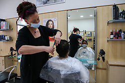 © Licensed to London News Pictures. 12/04/2021. London, UK. A woman gets her hair cut in a beauty salon on Green Lanes in Haringey, north London, which reopens after 4 months of Covid-19 lockdown. Cafes, restaurants, pubs, non-retail business and hairdressers across the UK closed following third national lockdown on 6 January, after a surge of coronavirus infections and hospital admissions across the UK. As restrictions are eased, cafes, restaurants, pubs, non-retail business and hairdressers reopen today.<br /> Photo credit: Dinendra Haria/LNP