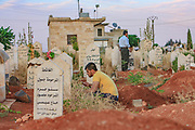 Relatives attend at the cemetery to mourn and pray for the dead body of 70-year-old Amina Ahmed Kabso at a cemetery in Tall Rifat village near Aleppo on Saturday, June 23, 2012. Kabso was killed in the latest spate of violence in northern Syria. Kabso was reportedly killed while traveling from Aleppo to her home in Tall Rifat when Syrian security forces targeted the mini-bus she was in. (Photo by Vudi Xhymshiti)