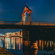 www.aziznasutiphotography.com                            This picture shows two bridges over Trondheim river which is called Nidelva. Gamle bybro or Old town bridge has the best view over Trondheim famouse warehouses. The second one which is further away in this picture is called Bakke Brua. Between these two bridges the Bryggene with all those wooden colorful houses are located which are one of the main tourist attraction in the town.