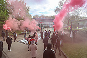 """Leicester, United Kingdom, May 19, 2021: People hold red flares as they gathered to support UK based Pro-Palestinian activists group """"Palestine Action"""" who seized control of the Leicester based factory of Elbit subsidiary UAV Tactical Systems on Wednesday, May 19, 2021. Activists say that """"the occupation is aiming to be as disruptive as possible; these activists are determined to prevent Elbit from resuming its business of bloodshed."""" (Photo by Vudi Xhymshiti/VXP)"""