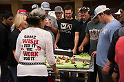 The Iraan High School football team checks out a cake decorated with the bus the team will take to Arlington and the trophies they plan to win during a community dinner in Iraan, Texas on December 13, 2016. (Cooper Neill for The New York Times)