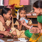 CAPTION: After-School Club (ASC) Coordinator Asha, who herself has scoliosis, leads children in a card game. The game is very visual, designed to be inclusive for those children who struggle to recognise words. LOCATION: Heggotara (village), Kasaba (hobli), Chamrajnagar (district), Karnataka (state), India. INDIVIDUAL(S) PHOTOGRAPHED: From left to right: Megha M., Chennanjamma and Asha.